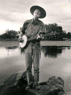 "Pete Seeger whose banjo reads, ""This machine surrounds hate and forces it to surrender."" (a counterpoint to Woody Guthrie's famous guitar. rw)"