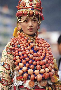 Ngawa, Amdo, Tibet | Woman from Ngawa dressed in her family treasures of coral, gold, silver and other jewelry. This lady probably wears 10 to 15kg of coral necklaces alone (the rest of her jewelry worn on her back and below the waist might be the same again!), so must get very tired after hours of wearing all this! That's why dressing up like this happens only once a year at most. Both the silver belt with huge inlaid coral, and the headdress are style special to Ngawa. Photographer: ?