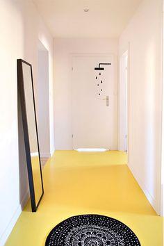 Ten minimalistyczny przedpokój nabrał charakteru dzięki wyrazistej żółtej podłodze skontrastowanej z czarnym dywanem i ramą lustra. To ostatnie oparto o ścianę, zamiast na niej wieszać, dzięki czemu aranżację można łatwo zmieniać. Naklejka na drzwiach łazienki sygnalizuje przeznaczenie pomieszczenia.