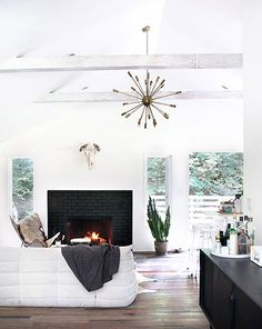 The Best Bright White Spaces//black fireplace, sputnik chandelier, white sofa, bar