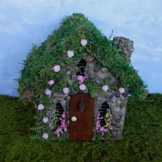 Welcome and thank you for visiting my shop. It brings me great solace when Im making my fairy garden items or puttering in my miniature garden. It is my sincere wish my work brings you some comfort and joy to!  Sure to attract fairies to your garden with this charming fairy house! This lovely little stone fairy house has three arched windows filled with flowers and climbing light pink roses. A stone chimney, tiny pine cone on the door and a preserved moss roof give this house its old world…