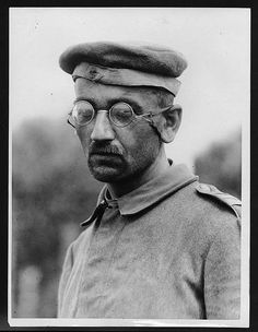 Type of German prisoner captured in the new push (1918)        Type of German prisoner captured in the new push    German prisoner, during World War I. He is wearing a cloth or wool cap and a tunic style jacket. His spectacles, held on by 'ear-bands', reflect the scene in front of him. The closeness of the subject forces one to look at his face and into his eyes.
