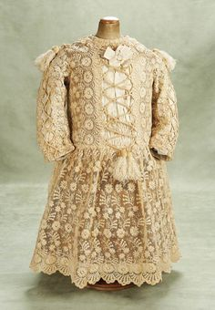 Very Beautiful Embroidered Lace Child's Dress for Larger Bebe. A very fine dress of embroidered tulle lace,the dress features long coat-style sleeves,scalloped-edgehem,and is decorated with ivory silk faille panels on the bodice and sleeves that are trimmed with criss-cross cording and velvet/silk tassels,fully-lined. Circa 1880. http://Theriaults.com/