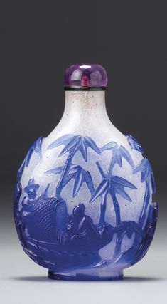 A SAPPHIRE-BLUE OVERLAY WHITE GLASS 'SCHOLAR IN BOAT' SNUFF BOTTLE QING DYNASTY, 18TH CENTURY
