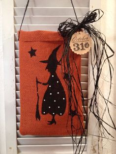 Our orange burlap ditty bag, is hand stamped and the tag also is hand stamped and has black raffia as a bow.