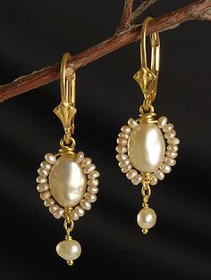 "A daisy of champagne pearls, these earrings feature a large champagne pearl nestled amongst a ring of seed pearl. Playful and elegant, these earrings will compliment any outfit and can easily be dressed up or down for any occasion. Available in 22kt gold vermeil or sterling silver, these earrings hang 1.5"" as shown on the tulip leverbacks. Also available in studs and French wires. $48 to $52"