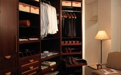 Dark Mahogany closet with pull out shelves and valet hook and swing rod. From Lisa Adams, LA Closet Design