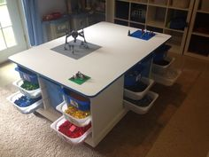 "Our ""ikeahacked"" Lego table for the littles. Three wooden Trofast cabinets stripped and painted, screwed to a piece of plywood, and trimmed out. Added 4"" wheels, lidded with white MDF, finished with rubber edging in a pretty accurate Lego blue."