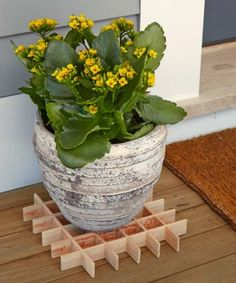 Repurpose paint stirrers to raise a planter (which will prevent deck stains and rot) by cutting notches every 1½ inches and assembling stirrers as shown.