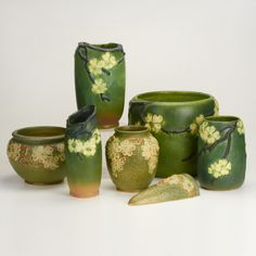 """ROSEVILLE Dogwood I and II, seven pieces: two jardinieres, four vases, and wall pocket Some marked Largest: 9 1/2"""" x 11"""" dia."""