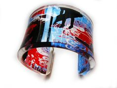 The image on this elegant acrylic cuff bracelet presents a graphic on the Berlin Wall. It was constructed in 1961 to separate Germany and Berlin during the Cold War. In the 1980s, the wall was reconstructed and graffiting on the wall became popular for artists from all over the world and a place where tourists would go and admire the artwork.