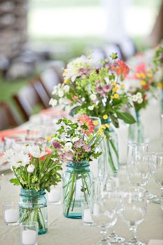 Love the mason jar idea! Centerpiece flowers include grasses, berries, flat parsley, golden sage, zinnias, dahlias, small green hydrangeas, orange lilies, baby's breath, phlox, snapdragons, peonies, lavender, and alstroemerias.