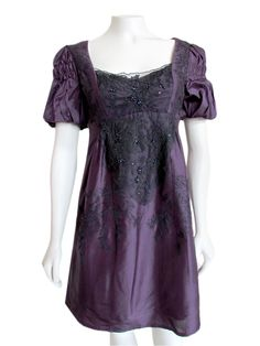 Breath a little romance into your wardrobe in this 'Juliet' inspired babydoll dress from Nanette Lepore. Made from a dark purple silk shantung material, and embellished with black floral lace, embroidery, and beading down the front; this dress features a babydoll silhouette with scooped neckline, empire waist seaming, and short smocked sleeves. Finished with a hidden back zip and full lining. Perfect paired with heels for an evening out, or layered under a long cardigan with leggings and…