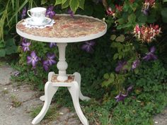 A small piecrust edge round table painted with Everlong Chalk Paint in 'Latte' and has the top covered in vintage wallpaper.