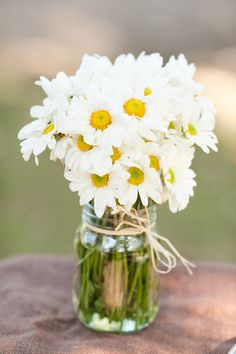 we love this idea so much-great for outdoor  or country inspired weddings. A bundle of daisies or lilies, a mason jar and a tiny piece of ribbon! Voila shabby chic!