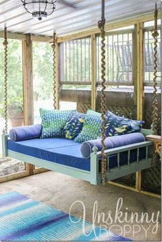 Pretty hanging bed on a screened-in back porch.  Love the wrapped rope around the chains.