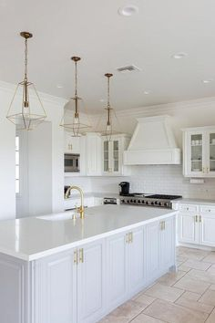 Three gold lanterns hang over a light gray island accented with brass pulls and a white quartz countertop fitted with an undermount sink with a brass gooseneck faucet.