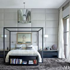 The master bedroom's walls are upholstered in an Élitis linen, and a Moooi light fixture is suspended above the BB Italia bed, which frames an artwork by Luis Caballero. The branchlike sconces are by Porta Romana