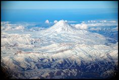 At a height of 5,670m, Mt Damavand is a volcano which somewhat anomolously sits within the fold and thrust belt of the Alborz Range, north of Tehran, Iran.   It is a large intraplate composite cone representing an accumulation of more than 400 km3 of trachyandesite lavas and pyroclastic material.  For more see:  http://www.tectonics.caltech.edu/meetings/brownbag/material/jamshid/i0016-7606-116-1-16.pdf