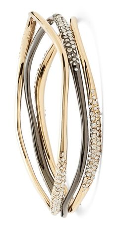 These sparkly gold and gunmetal bangles are all about sculptural lines and moody drama.