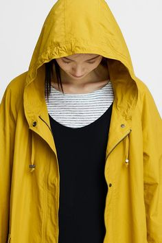 Organic Cotton Nylon Hooded Drawstring Jacket in an oversized A-line shape with hidden snaps and wide raglan sleeves.