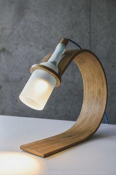 Luminaire recyclant une bouteille. La plaque de bois est cintrée, elle donne ainsi du mouvement à la lampe.  La torsion donne une certaine souplesse, une forme plus arrondie, plus douce. La torsion permet de d'apporter une esthétique plus douce et moins stricte qu'une simple plaque droite qui parait plus rigide.
