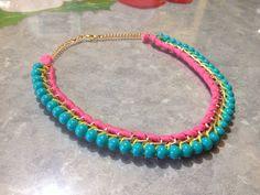 Collar con cadena color oro, tejido con hilo color rosa, amarillo y perlas color azul turquesa entrelazadas. Muy colorido y juvenil.