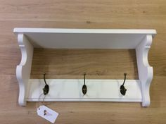 Made in my workshop in the East Sussex countryside a solid wood coat rack with shelf. Made from solid Tulip wood (Poplar) and painted in Mylands of London Whitehall.  3 Antique Brass Hooks.  60, 15.5, 31cm.  Fixed to the wall with two keyhole type fixings.  All fixings are included.