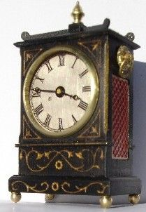 1:12th scale Georgian ebony working bracket clock. Hands are copies of the originals. It has brass side carry handles and a fretwork panel filled red to replicate silk. Halls Miniature Clocks.