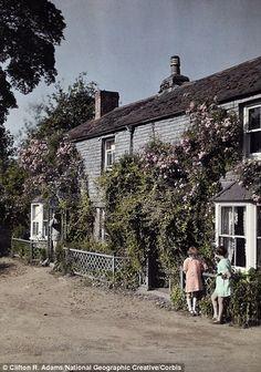 November 1928, Devon: Two young girls talk outside a home in Chillington, Devon..
