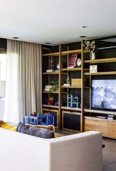 Playroom moderno equipado con mueble de TV en petiribí con cera natural (Mesopotamia), sillón (Abax) con almohadones de lino en dos tonos y con detalles bordados y apliques metálicos.