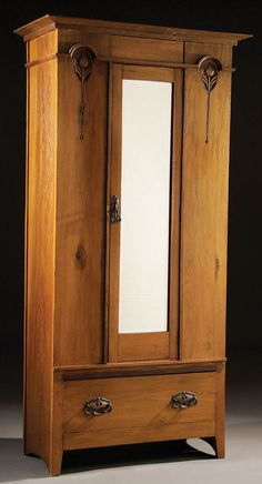 A CONTINENTAL ART NOUVEAU OAK WARDROBE, late 19th century, with stylized carved floral decoration and cast drawer pulls.