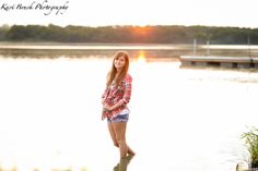 2015 High School Senior girl for posing picture ideas. Senior girl standing in the water by a beach or lake at sunset. Country girl type look. High school senior session pose inspiration for senior pictures. Kari Bruck Photography