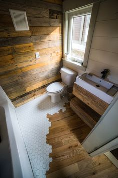 "The 3"" solid oak flooring transitions into geometric tile in the bathroom."