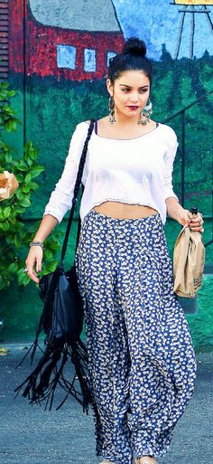 Vanessa Hudgens' Boho-style is exemplified in this outfit of printed pants, a crop top, fringed bag, and a high bun.
