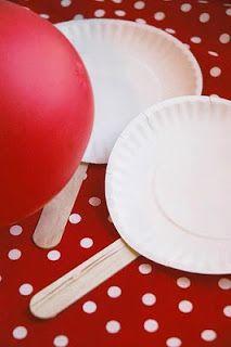 Ping Pong de bexigas com pratos de papelão. Pegue pratos de papelão e cole palito de sorvete em cada um deles. Ideia super criativa e divertida.