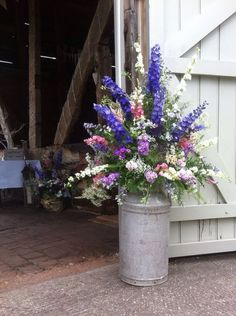 Country garden flowers arranged in milk churn