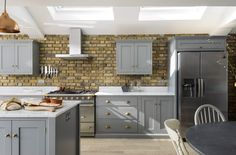 A beautiful sunny deVOL Shaker kitchen painted in Lead with brass handles and Carrara marble worktops