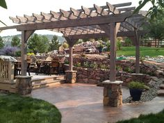 Rough-sawn timber Pergola, stone piers, rock retaining wall, stamped concrete patio