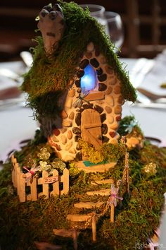 "A moss-covered cottage was just one of the eclectic ""enchanted garden"" themed wedding centerpieces. Pixie Vision Photography."
