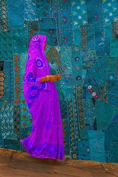 Woman walking past a tapestry, Jodphur, Rajasthan, India