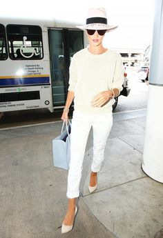 Rosie Huntington-Whiteley in a sweater, white pants, and white wide brim hat