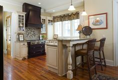 Eastover Cottage traditional kitchen.   Love the bar, the llarge windows over the sink.. and of course the stove.  I know it needs a refrigerator, and ovens,..but this is a great start to an open kitchen.  Very nice.