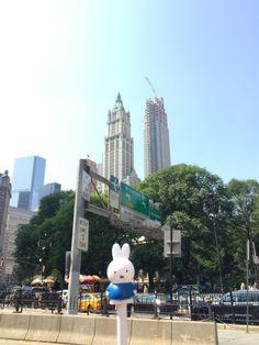 Nijntje heeft van Miranda haar eigen selfie-sta-op-de-stok gekregen, maar blijft toch klein in verhouding tot alle grote en hoge gebouwen op de foto.