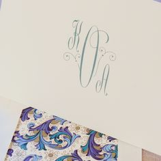 Avalon Monogram Ecru Note: One's monogram should always reflect the personality of the correspondent. Presented with delicate flourishes in rich peacock ink, this particular option should be reserved for the true romantic. Pair with our Blue Green Florentine envelope lining for extra charm.