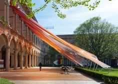 Coloured streamers erupt from arches of a palazzo facade to create this undulating canopy designed by MAD
