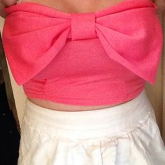 Coral bow crop top  Coral color. Super cute. Strapless. Has a big bow on the front. Looks great with high waisted skirts and pants!! Especially with anything white! Bought from pacsun.  86% polyester. 12% rayon. 2% spandex.  Worn once. Only thing is there was a tear on the seem up the front so I sewed it up. PacSun Tops Crop Tops