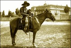 A man and child sit on a horse in front of the St. Ignatius Mission, Flathead Indian Reservation in western Montana on the Flathead River. Home to the Bitterroot Salish, Kootenai, and Pend d'Oreilles Tribes - also known as the Confederated Salish and Kootenai Tribes of the Flathead Nation. The reservation was created through the July 16, 1855, Treaty of Hellgate. Photographed between 1905 and 1907.