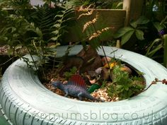 Outdoor Small world. Dinosaurs, gravel, tyre, plants. Engaging boys in imaginative play.