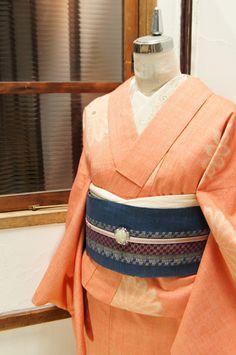 生成り色とオレンジの色糸で織り出されたシャーベットのような綺麗色に、デイジーのような大輪の花模様がふわりと浮かぶウールの単着物です。